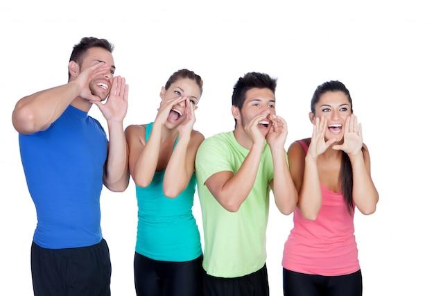 Amigos felices con el grito coloreado de la ropa de deportes aislado en el fondo blanco