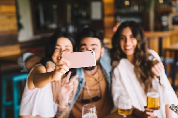 Amigos felices haciendo un selfie en bar