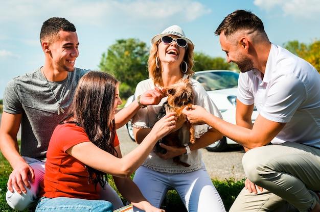 Amigos felices con lindo perro al aire libre