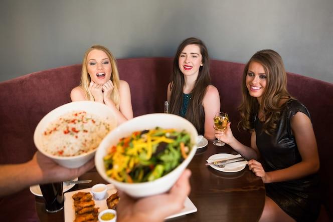 Amigos felices mirando la ensalada