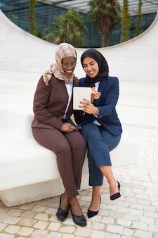 Amigos felices de la oficina femenina viendo contenido en tableta