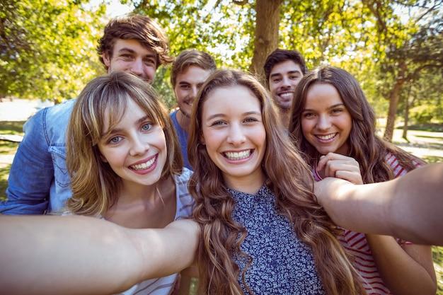 Amigos felices en el parque tomando selfie