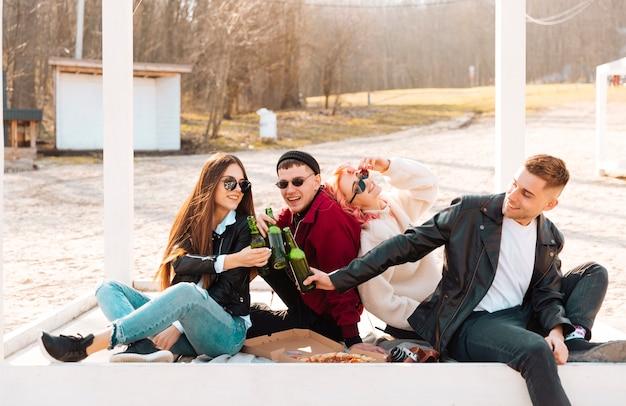 Amigos felices en picnic tintineando cerveza