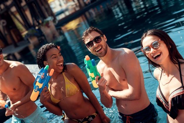 Amigos felices de pie juntos con pistolas de agua de colores
