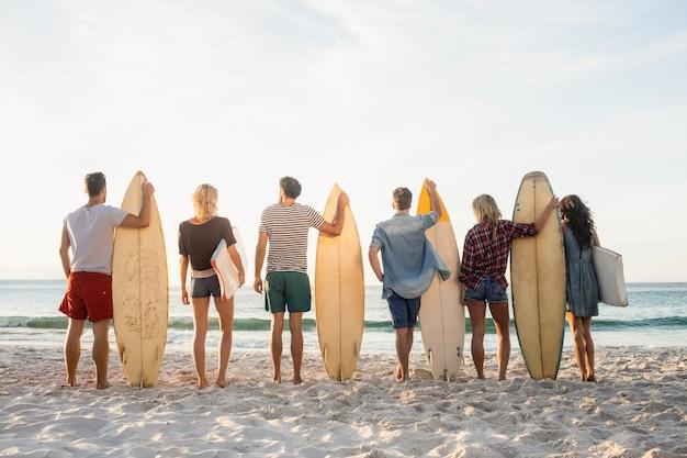 Amigos felices de pie en línea con tablas de surf