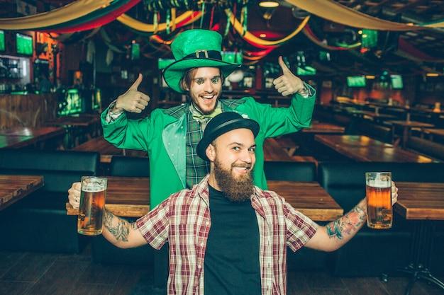 Amigos felices de pie en el pub y posan. se ven bien. chico de traje verde muestra sus grandes pulgares hacia arriba. joven delante tiene dos jarras de cerveza en las manos.