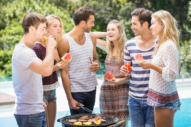 Amigos felices preparando barbacoa cerca de la piscina