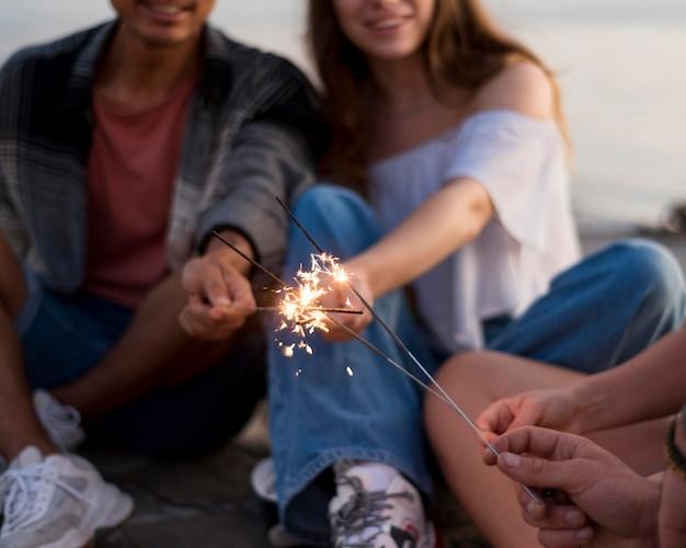 Amigos felices con primer plano de fuegos artificiales