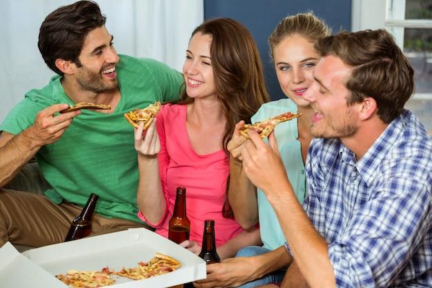 Amigos felices que comen pizza