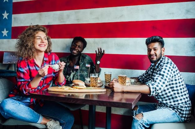 Amigos felices que descansan juntos en el bar, mujeres y hombres en el café, hablando, riendo comen comida rápida.