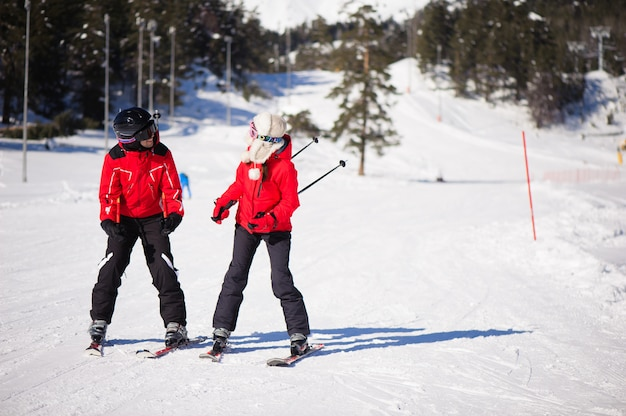 Amigos felices que se divierten en la estación de esquí de las montañas - imagen de naturaleza y deporte.