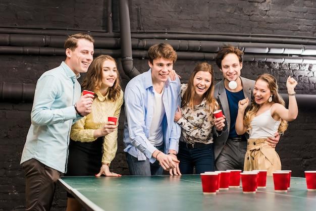 Amigos felices que miran la bola mientras que hombre que juega el pong de la cerveza en la tabla