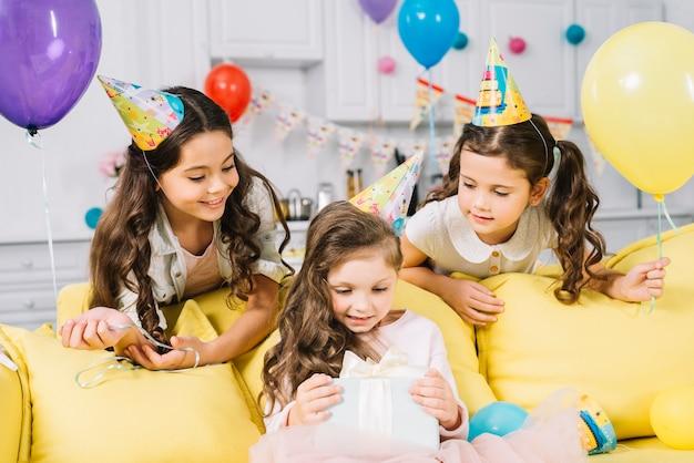 Amigos felices que miran a la muchacha del cumpleaños que abre el presente en casa