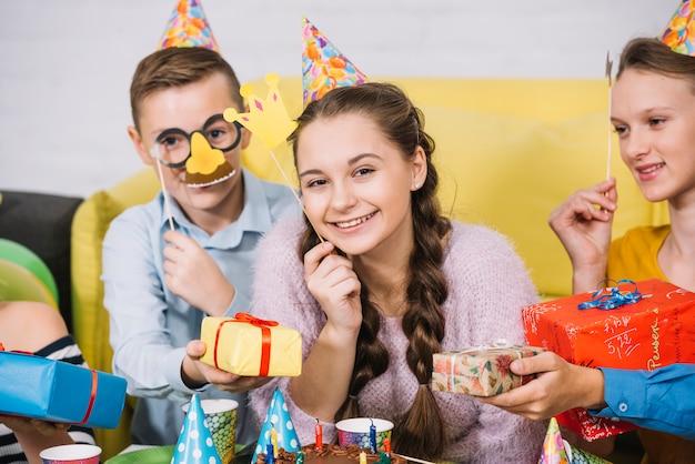 Amigos felices que sostienen los apoyos en la mano que dan regalos a la adolescente sonriente