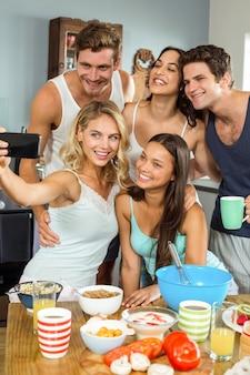 Amigos felices que toman selfie mientras cocina en la cocina