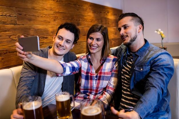 Amigos felices que toman selfie en restaurante