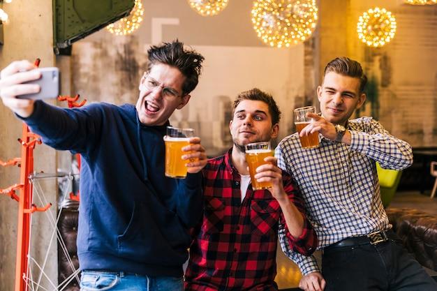 Amigos felices que toman el selfie en el teléfono móvil que sostiene los vasos de cerveza