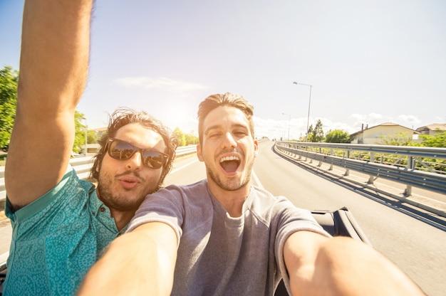 Amigos felices que se toman una selfie en un viaje en automóvil: dos turistas caucásicos que viajan alrededor del mundo