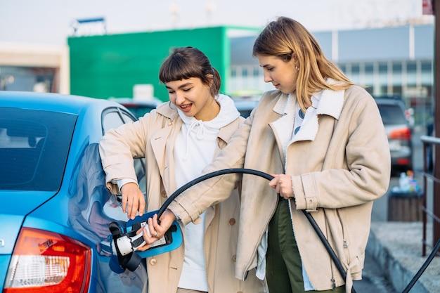 Amigos felices repostar el coche en la gasolinera.