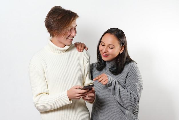 Amigos felices riendo y mirando un teléfono inteligente en blanco