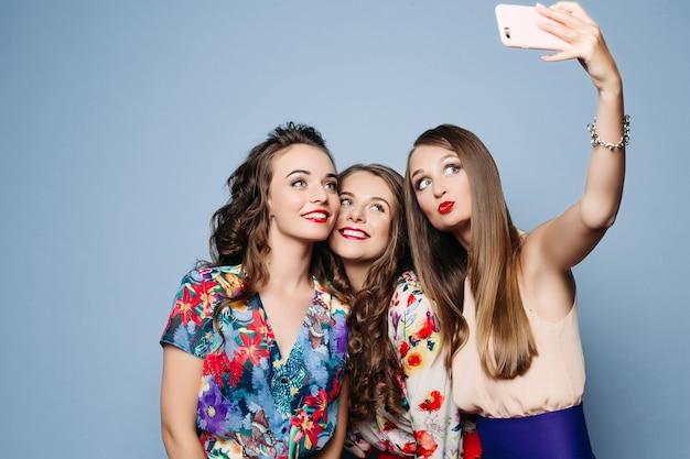 Amigos felices en ropa de moda tomando selfie sobre backgrou azul
