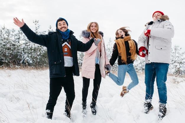 Amigos felices saltando en el bosque de invierno