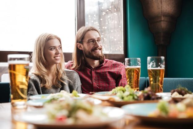 Amigos felices sentados en la cafetería mientras comen y beben alcohol