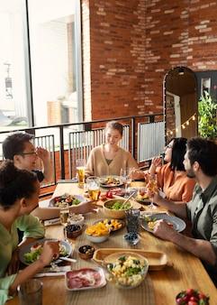 Amigos felices sentados en la mesa