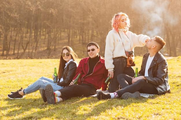 Amigos felices sentados en el pasto con cerveza y divirtiéndose