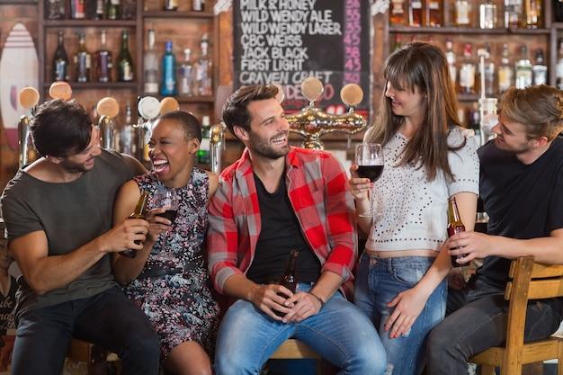 Amigos felices sosteniendo botellas de cerveza y copas de vino