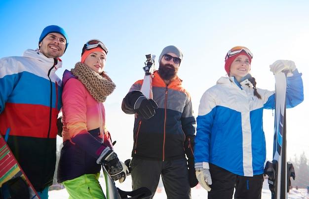 Amigos felices con tablas de snowboard y esquís