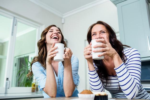 Amigos felices con tazas de café en la mesa