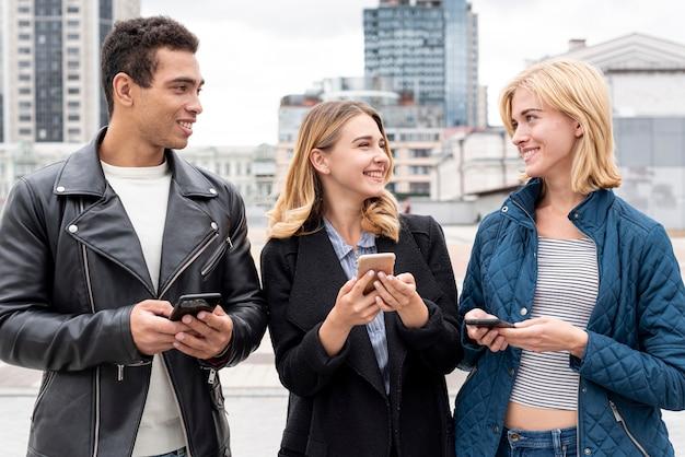 Amigos felices con teléfonos móviles