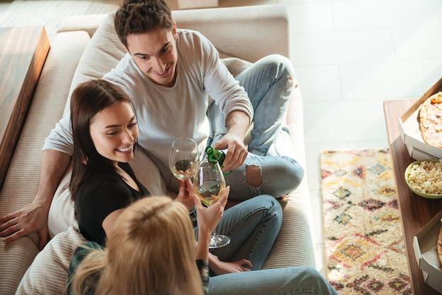 Amigos felices tintineando dando tostadas y tintineo de vasos en el sofá