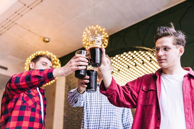 Amigos felices tintineando vasos de cerveza en el bar