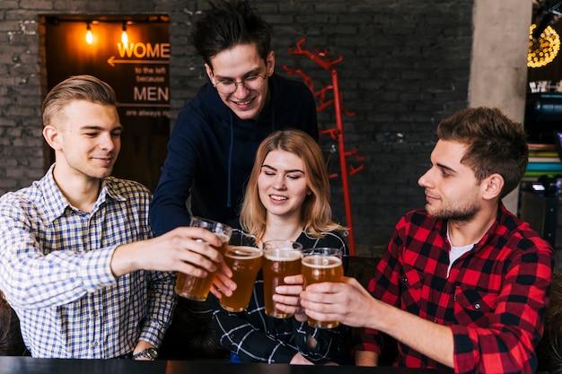 Amigos felices tintineando los vasos de cerveza en el restaurante