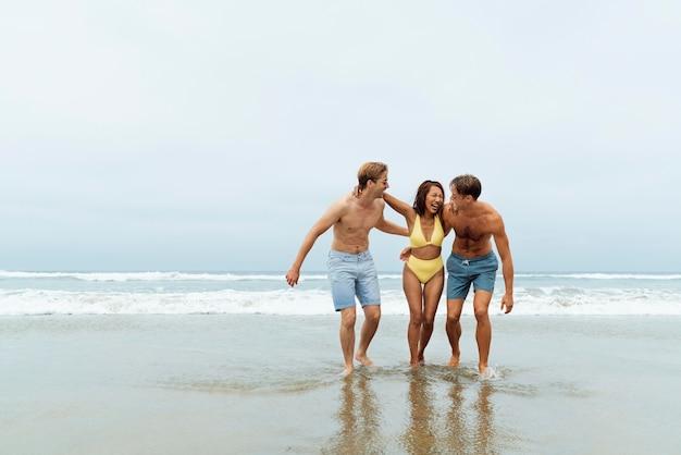 Amigos felices de tiro completo en la playa