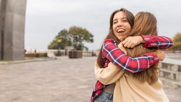 Amigos felices de tiro medio abrazándose afuera