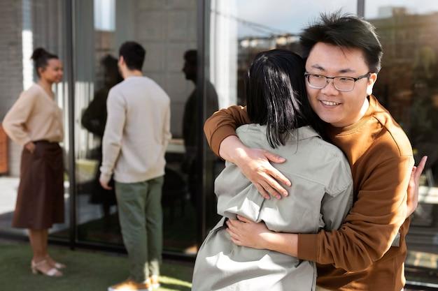 Amigos felices de tiro medio abrazándose