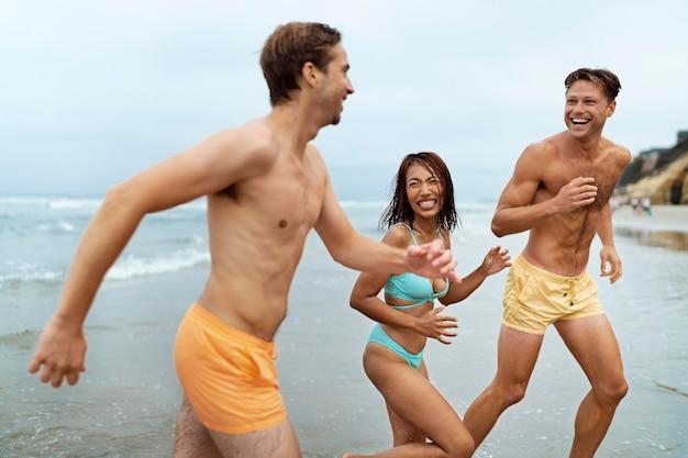 Amigos felices de tiro medio corriendo en la playa
