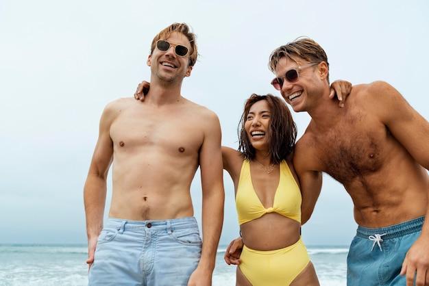 Amigos felices en tiro medio junto al mar