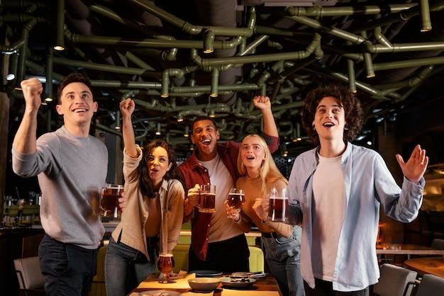 Amigos felices de tiro medio en el pub