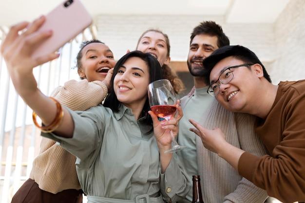 Amigos felices de tiro medio tomando selfies