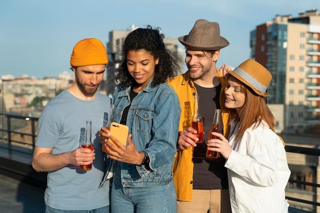 Amigos felices tomando selfie al aire libre tiro medio