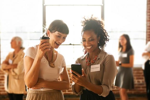 Amigos felices usando el concepto de redes sociales de teléfonos inteligentes