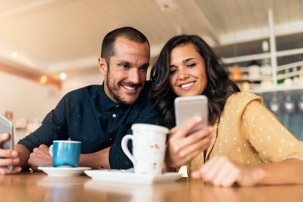 Amigos felices usando el móvil en la cafetería.