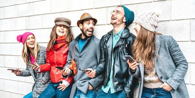 Amigos felices usando teléfonos móviles inteligentes en la pared de la universidad