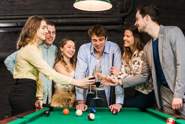 Amigos felices del varón y de la hembra que tuestan el vino en club sobre la mesa de billar en club