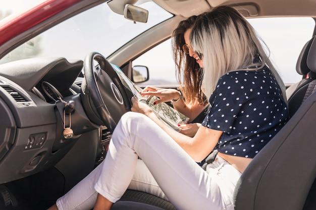 Amigos femeninos modernos que se sientan en el coche que busca destinos en el mapa