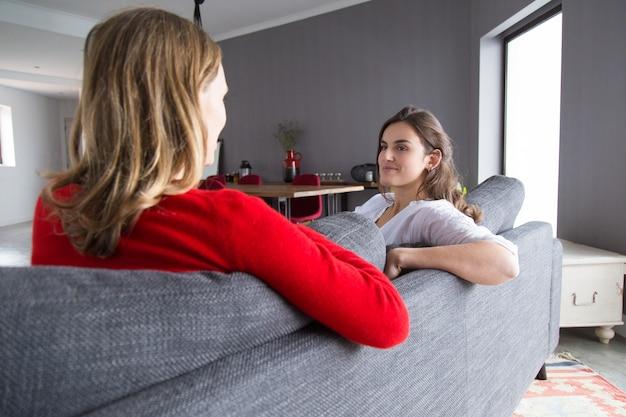 Amigos femeninos positivos reunidos en casa para charlar
